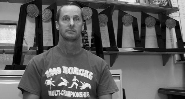 Coach Rick Anderson stands in front of the many trophies won over the years. (Photo by Bryce Fraser)