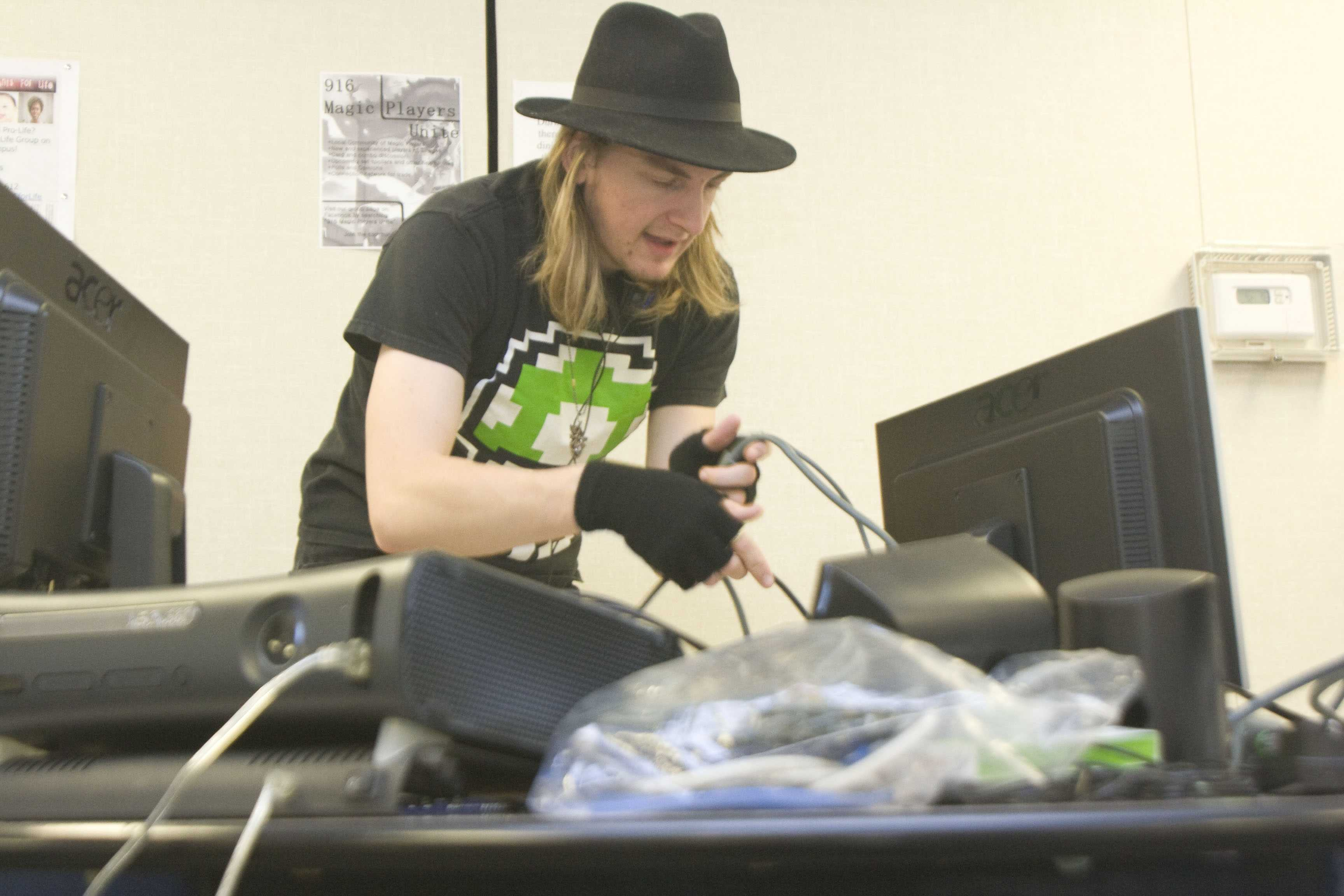 Psychology major Andrew Preston hooks up the wires to connect a PS3 and Xbox 360 console to the back of his computer monitors in the portable cafeteria on Nov. 22, 2011. (Photo by Demetric Good)