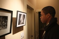 Gavin McIntyre, a student with art in the show, examines another student's photo on Feb. 11 at the Union Hall Gallery in downtown Sacramento.