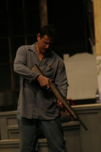Brandon Lancaster as Atticus Finch with a prop rifle during rehersal on Feb. 13.