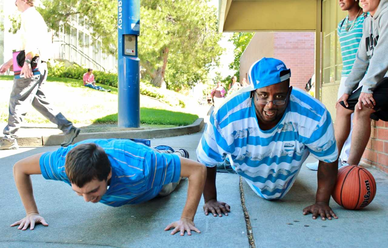 "David Himojosa (left, Sport Science major) and Carter ""The President"" French (right, Diesel Mechanics major) jokingly challenge each other to a push up contest outside the liberal arts building near the Rose Marks Pavillion on Thursday, August 29. (Photo by Emily K. Rabasto)"