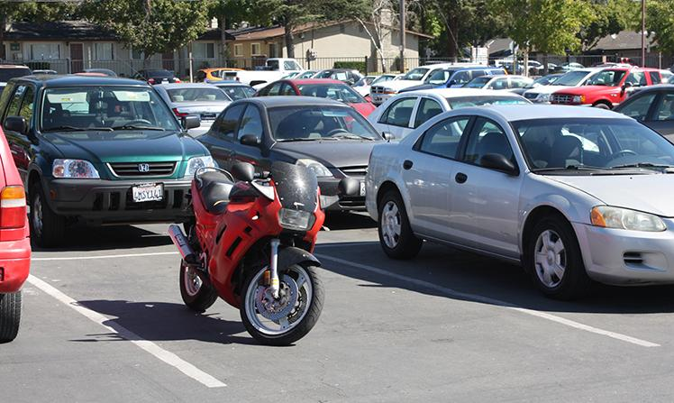 "A motorcycle parked between cars on August 29, 2013. According to Los Rios Police Department policy, ""Motorcycles may not park in regular vehicle spaces."" ARC has motorcycle parking in lots A, C and G. (Photo by Alex Panasenko)"