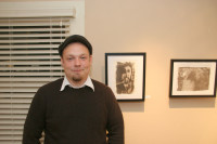 "Photography major Tysen Cannady next to his artwork titled ""Impending Doom"" at the exhibit on K street"