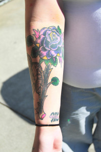Celah Adkins shows a cover up tattoo of a rose on her right forearm