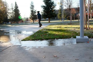 Dawn Benjamin from Los Rios Facilities works to turn off the sprinkler system that malfunctioned, spilling water onto a campus walkway today.