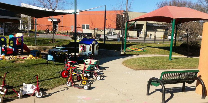 One of the outdoor play areas for the children features toys and tricycles for them to play with while being cared for.