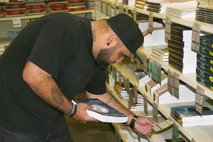 "Jimmy Espinosa, aka ""Pro Mañon,"" American River College student, commercial music recording major, on Jan. 31, 2014, checking out the books for his class. Espinosa considered either purchasing or renting textbooks for his classes. (Photo by Alex Panasenko)"