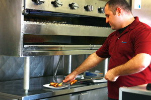 """Armenian native """"Andy"""" Andronik Muradyan removes chunks of fire-roasted chicken breast, the restaurant's bestseller. Muradyan and his family have owned Royal Kebab for more than two years."""