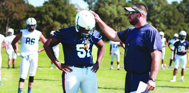 New Head coach Jon Osterhout explains the details of a play to the football team during the first practice of the season.