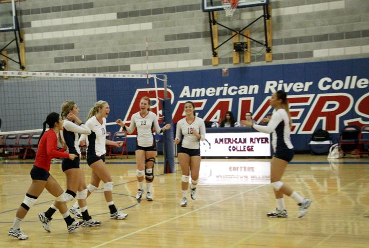 The Women's Volleyball team celebrate after a successfully rallied and scored against the opposing team. (Photo by Brandon Nelson)