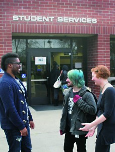 Student helper and part-time clerk Brandon January, 25, relays financial aid information to passing students Billow Bowles, 28, majoring in Art New Media, and Alycia Riggins, 27, majoring in Funeral Services.