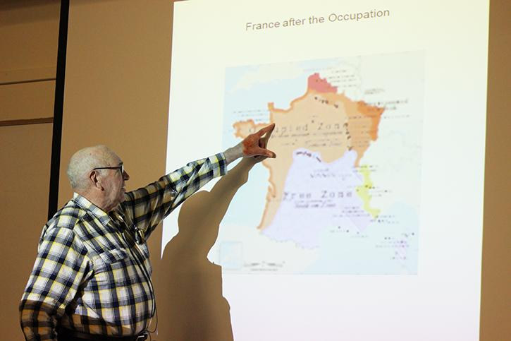 Conrad Tracy, husband of Holocaust survivor Renee Heck, shows the audience the approximate location of where Heck and her mother escaped to in France when they left their home in Germany. Tracy shared the story of his wife, who had passed last spring, during an event that remembered survivors of the Holocaust.