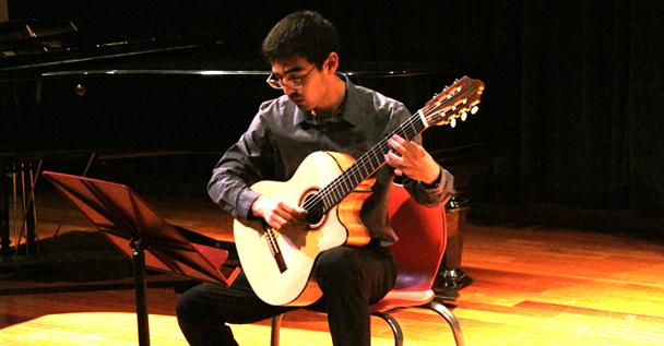 """American River College student, Eric Kuvakos strums the guitar to the musical piece, titled """"Round Midnight"""" during last Friday's music recital."""