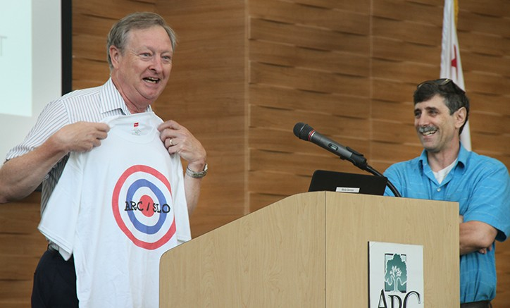 John Gamber, left, receives a shirt from fellow employee Randy Schuster at ARC's Fall 2015 Convocation for consistently 'hitting the target.' Said Gamber: 'As someone who wore camouflage for 15 years, I cannot tell you how nervous this makes me.' (Photo by Kameron Schmid)