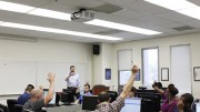 Students participate by raising their hands during Professor Michael Spurgeon's American River Review class. The ARR course is based around reviewing student submissions such as poetry, fiction, creative non-fiction etc. and active involvement is expected. (Photo by Cheyenne Drury)