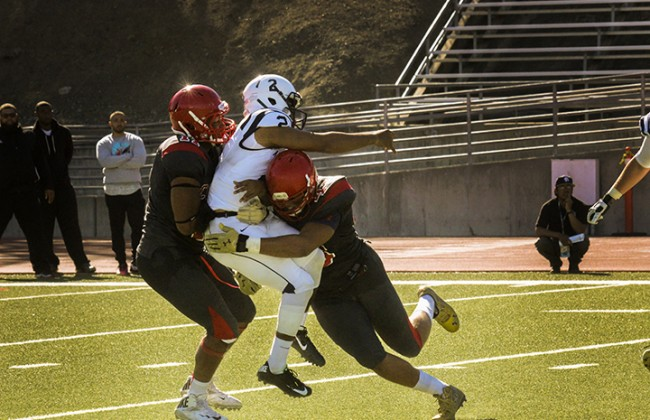American River College's quarterback Jihad Vercher getting tackled by City College of San Francisco defensive ends Rod Jones and Austin Larkin during ARC's 20-17 win over CCSF on Sat. Sept. 26, 2015. The game ended with ARC beating CCSF 20-17. (Photo by Ashlynn Johnson)