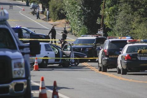 A police officer photographs the crime scene on Cypress Avenue near Garfield Avenue on Thursday. (Photo by John Ferrannini)