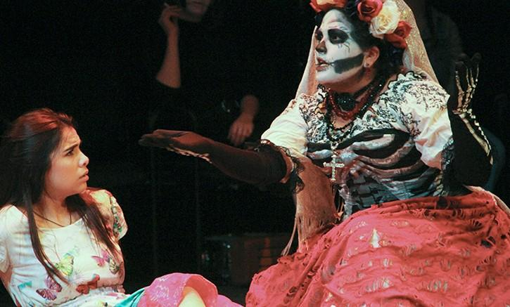 Maya (played by McKenzie Lopez), left is visited by Santa Muerte (played by Itzin Alpizar) after praying that her dead mother's soul is left restless. The play will run until Dec. 6. (Photo by Joseph Daniels)