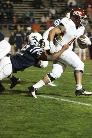 Defensive lineman Quincy Capel of American River College grabs at the jersey of Sacramento City College running back Leonard Skattebo in attempt to drag him to the turf. Capel had three tackles in ARC's 38-18 win on Nov. 14, 2015. (Photo by Nicholas Corey)