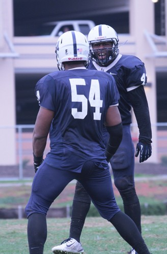 Former American River College football player Antonio Perez (54), seen celebrating with teammate Lawrence Hall during 2014,