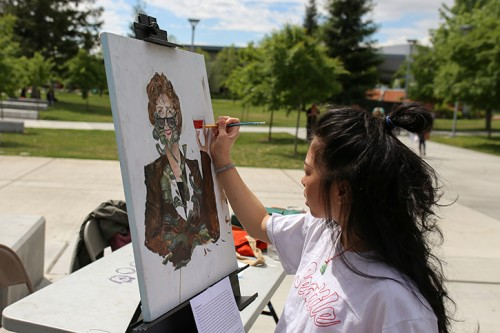 "American River College student Kashia Lynhiavue paints one of her works titled ""Linda Katehi"" during the Artivism event held by UNITE at American River College on April 27 2016. The event featured local activists, visual artisits and live performers. (Photo by Kyle Elsasser)"