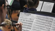 "The sheet music for ""Light Cavalry Overture"" by Franz von Suppe is seen over the shoulder of a violin player from the American River College Orchestra at their March 30 practice. The orchestra recently welcomed four primary school musicians to their practice. (Photo by Hannah Darden)"