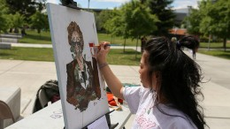"American River College student Kashia Lynhiavue paints one of her works titled ""Linda Katehi"" during the Artivism event held by UNITE at American River College on April 27, 2016. The event featured local activists, visual artisits and live performers. (Photo by Kyle Elsasser)"