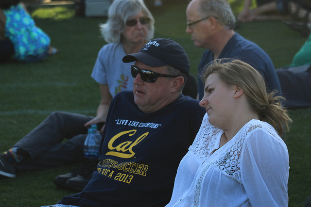 "Kevin Bell (left) and Brigid Bell (right) sit on Bonney field at Cal Expo waiting for Bernie Sanders to give his speech at his ""A Future to Believe In"" rally on May 9, 2016. Brigid is a first time voter who hopes her undecided father chooses Sanders.(Photo by Robert Hansen)"