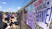 One of the many signs brought to the Sacramento Bernie Sanders rally hangs along a fence in front of the line forming at Bonney Field in Cal Expo. The line started forming around 8 a.m. and the doors open at 5 p.m. (Photo by Hannah Darden)