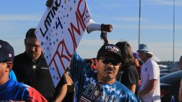 """A Donald Trump supporter holds up a sign reading """"Latinos 4 Trump"""" in line to hear the presidential hopeful speak. (Photo by Jordan Schauberger)"""