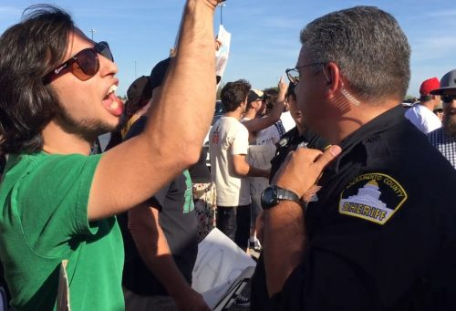 A protester shouts over a police officer at Trump supporters as the file into Trump's rally in Sacramento. (Photo by Jordan Schauberger)