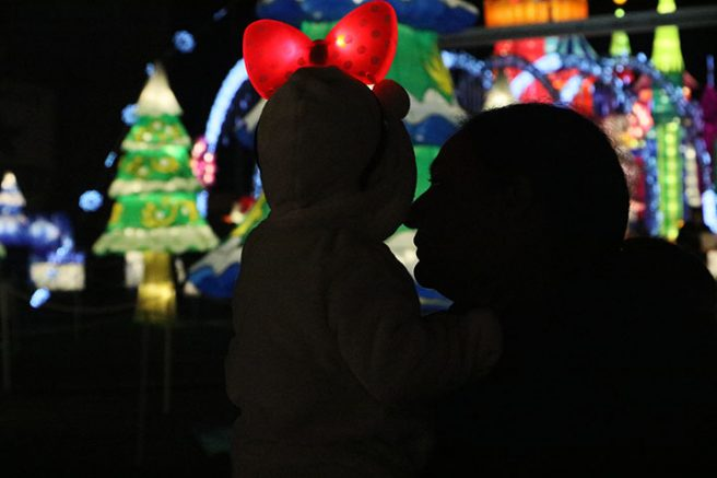 "A woman looks at the child she is holding at ""Global Winter Wonderland"" at Cal Expo on Sunday in Sacramento, Calif. (Photo by Cheyenne Drury)"