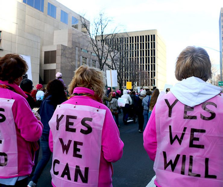 "Three women sport their homemade signs worn on their backs  at ""Women's March on Sacramento,"" a nationwide peaceful gathering to show support for all marginalized peoples in downtown Sacramento on Saturday. The event was coordinated by Jessica Browning, Sarah Linder, Annie Adams, and Sita Wilson Stukes. (Photo by Cheyenne Drury)"