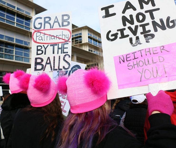 "Three women wear matching pink beanies and hold signs at ""Women's March on Sacramento,"" a nationwide peaceful gathering to show support for all marginalized peoples in downtown Sacramento on Saturday. The event was coordinated by Jessica Browning, Sarah Linder, Annie Adams, and Sita Wilson Stukes. (Photo by Cheyenne Drury)"