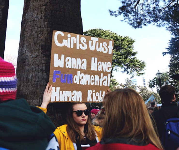 "A women holds leans against a tree and holds up a sign that rests on the top of her head at ""Women's March on Sacramento,"" a nationwide peaceful gathering to show support for all marginalized peoples in downtown Sacramento on Saturday. The event was coordinated by Jessica Browning, Sarah Linder, Annie Adams, and Sita Wilson Stukes. (Photo by Cheyenne Drury)"