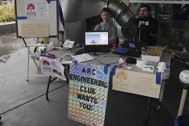 """Jacob Olson (left) and Ben McNeilley (right) are shown sitting outside in the rain promoting for the American River College Engineering Club. The sign they have posted says """"ARC Engineering Club Wants You."""" (Photo by Mychael Jones)"""