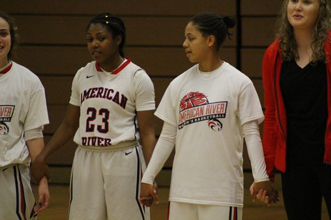 Alana Myers (left) and Deja Samuels (right) join hands during the national anthem before the game starts. (Photo by T.J. Martinez)
