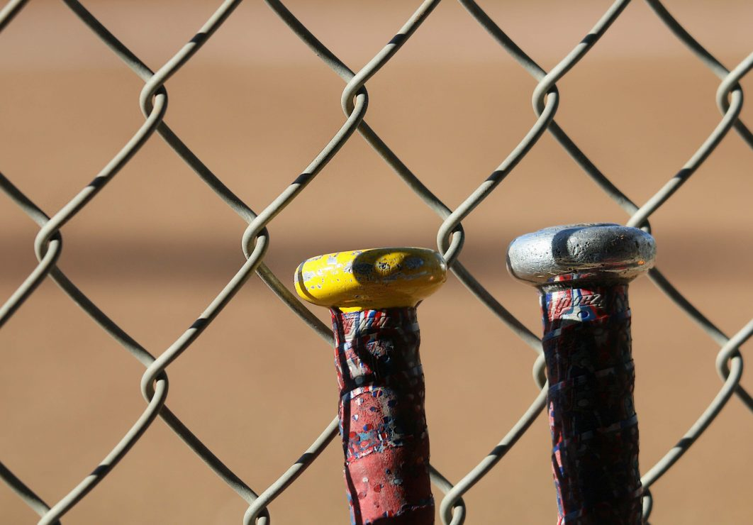 Softball bats lean against the fence. (photo gallery by Lidiya Grib)