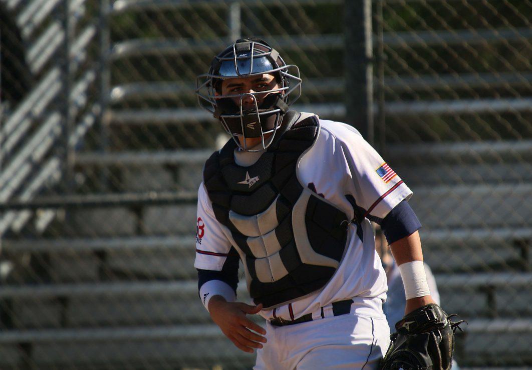 ARC baseball catcher stands behind first base.