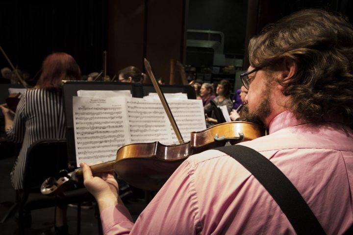John Hering looks at his sheet music as he plays his violin during the American River College Orchestra's rehearsal on Mar. 8 at American River College.(Photo by Ashley Hayes-Stone)