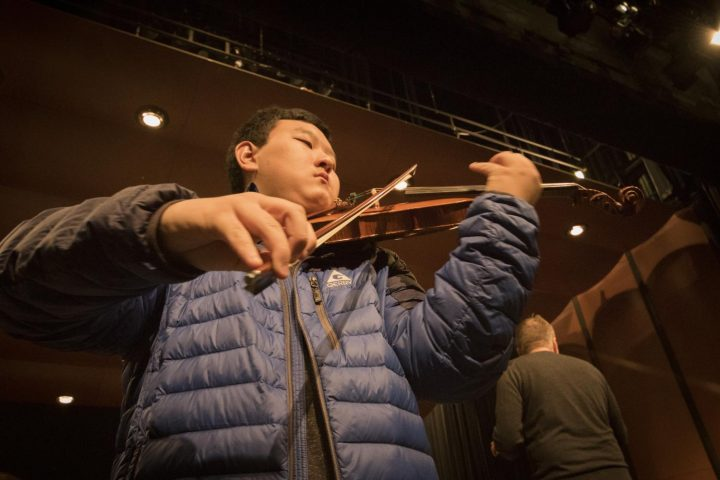 Anthony Zhao plays the lead violin during the rehearsal on Mar. 8 at American River College. (Photo by Ashley Hayes-Stone)