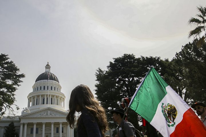 Protesters carry a Mexican flag outside of the California State Capitol on March 31, 2018.