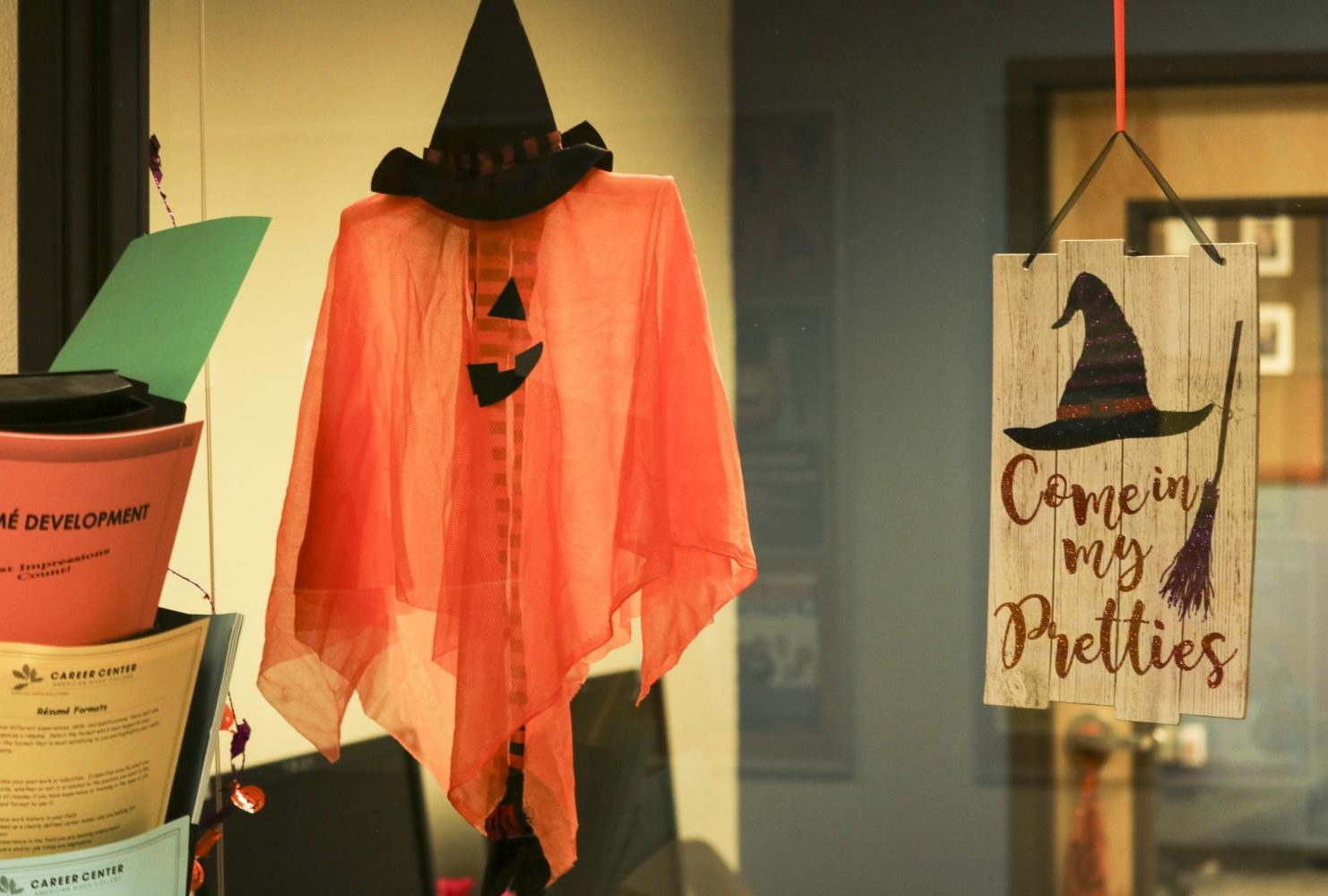 The Career Pathway Support Services hangs up witch themed decortions for the department Halloween contest. (Photo by Gabe Carlos)