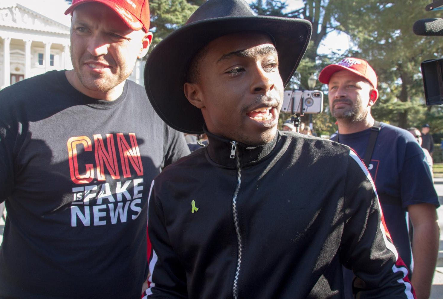 "Stevante Clark, who gained notoriety in March 2018 while protesting the shooting of his brother Stephon Clark, speaks to ""Turn California Red"" conservative rally organizer Ben Bergquam at the California State Capitol on Nov. 4, 2018. (Photo by Patrick Hyun Wilson)"