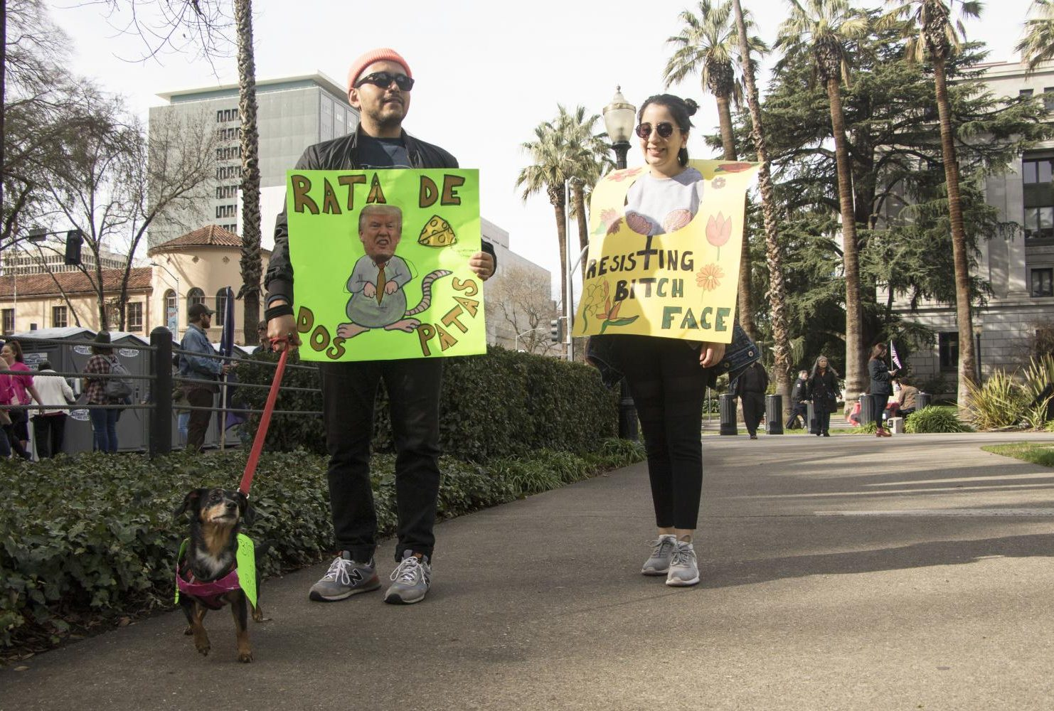 "A demonstrator holds a sign that reads ""Rata De Dos Patas"" which translates to two legged rat as another participant wears her sign that reads ""Resisting Bitch Face"" at the California State Capitol during the third annual Women's March."
