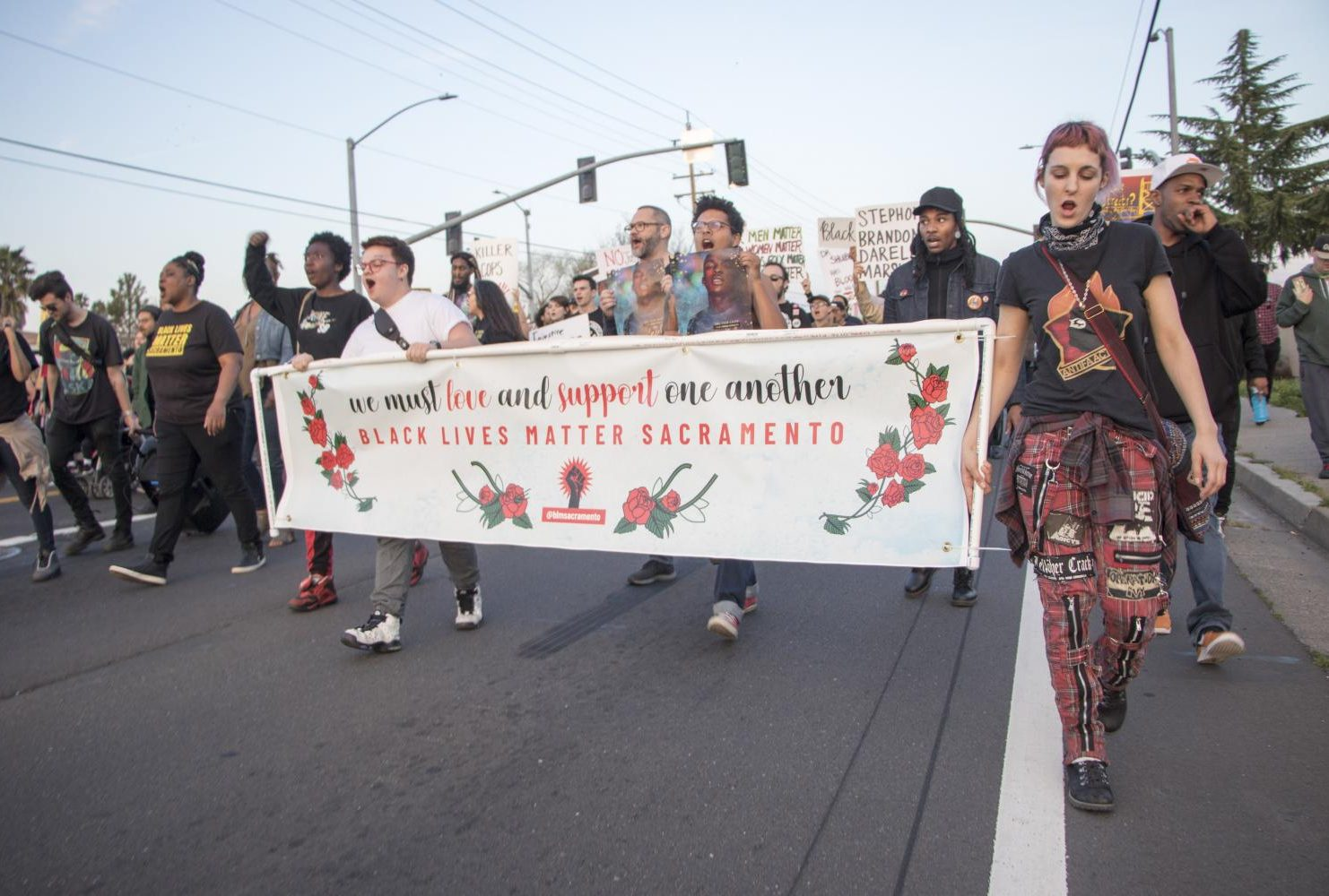 """Demonstrators hold up a sign that reads """"We must love and support one another / Black Lives Matter Sacramento"""" banner during the one year anniversary of Stephon Clark's death in South Sacramento, Calif. on March 18, 2019. (Photo by Ashley Hayes-Stone)"""