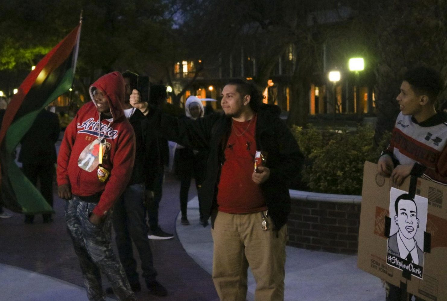 """Donovan Anvrave, a student at the vigil, holds up an iPhone, asking the crowd """"Is this a gun?"""" at Sacramento City College on March 7, 2019. His chant was a reference to the phone Clark held that police officers reportedly mistook for a gun. (Photo by Hannah Yates)"""
