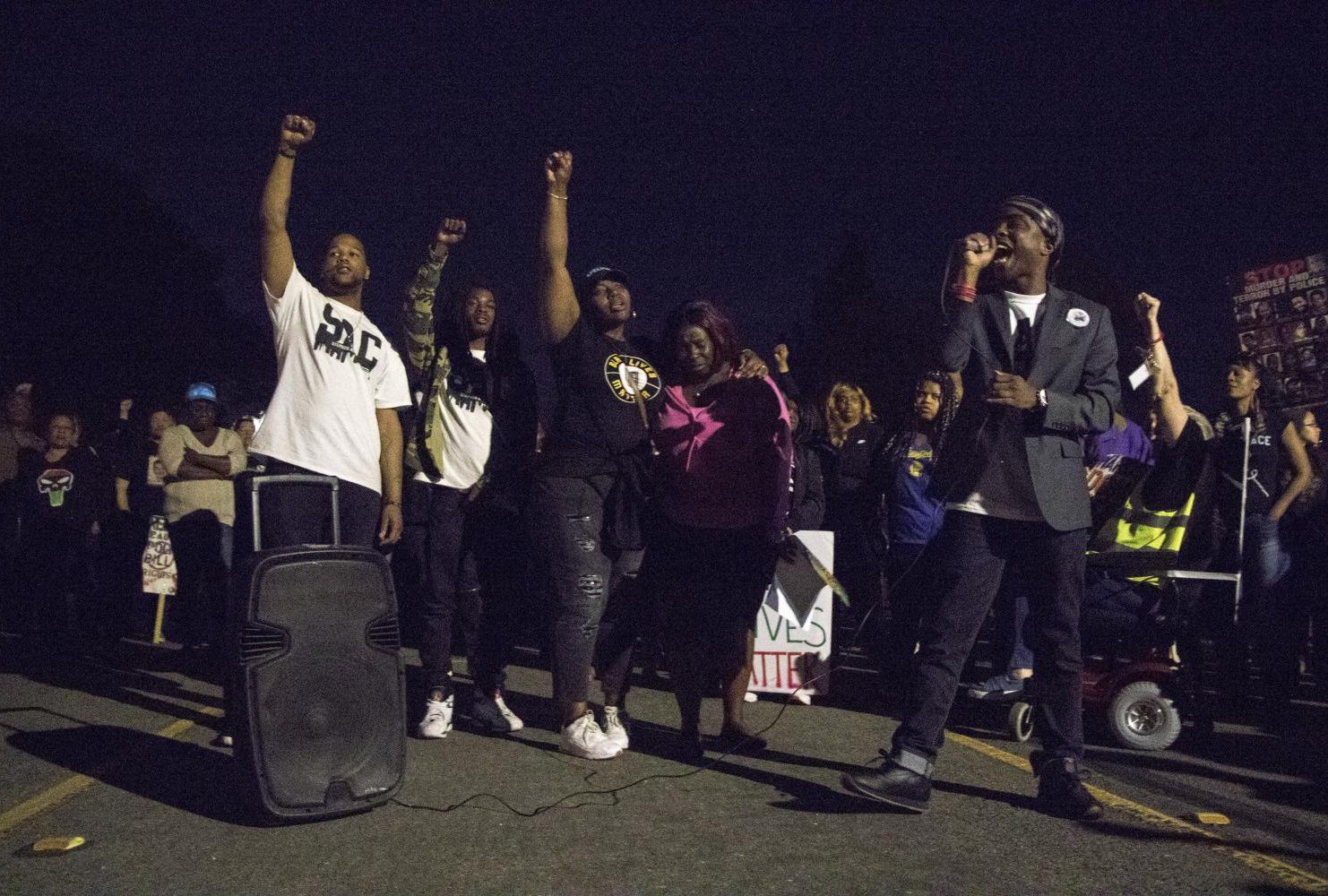 tephon Clark's brother Stevante Clark speaks into a microphone to a crowd of Black Lives Matter Sacramento demonstrators as members of the Clark family raise their fists in the background during the one year anniversary of Stephon Clark's death in South Sacramento, Calif. on March 18, 2019. (Photo by Ashley Hayes-Stone)
