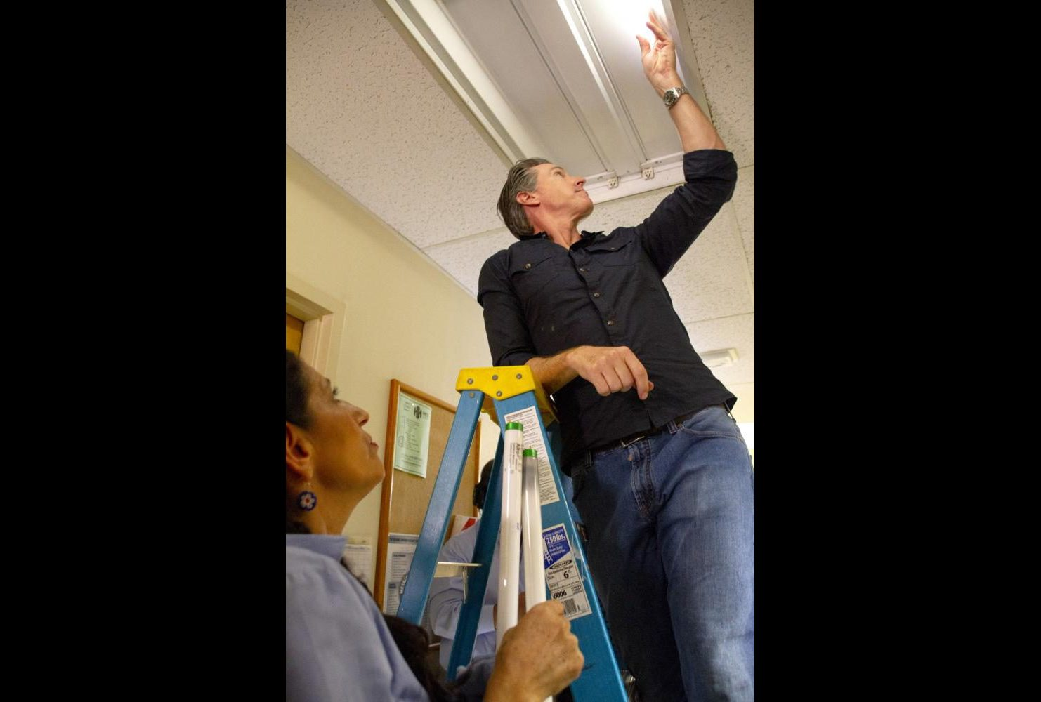 Calif. Governor Gavin Newsom replaces a florescent light bulb at American River College on the third floor of Davies Hall while shadowing custodian Maria Arambula for International Workers' Day on May 1, 2019. (Photo by Patrick Hyun Wilson)