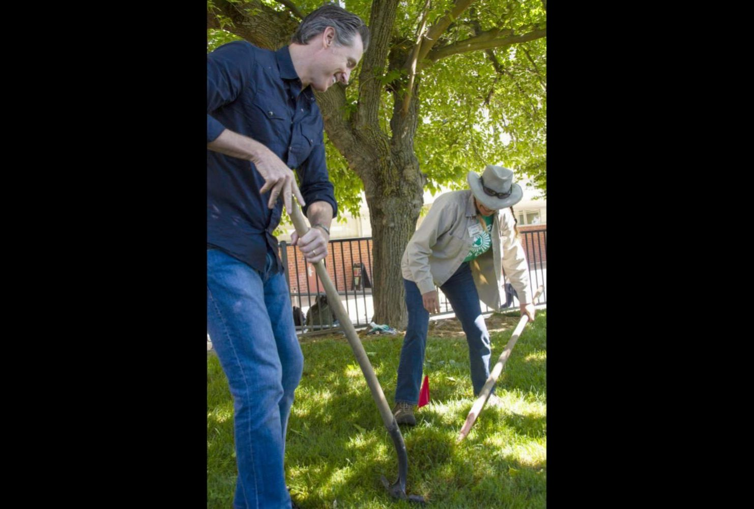 Calif. Governor Gavin Newsom assists groundskeeper Brenda Baker extend a sprinkler head at the Ranch House at American River College for International Workers' Day on May 1, 2019. (Photo By Patrick Hyun Wilson)